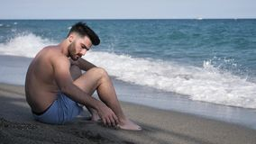 年轻人坐使用与沙子的海滩 股票录像