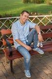 年轻人坐在公园和举行运动鞋的长凳新出生的 免版税图库摄影