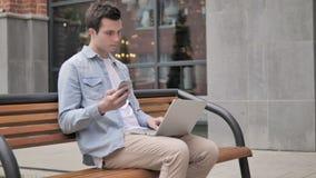 年轻人坐室外使用智能手机和膝上型计算机