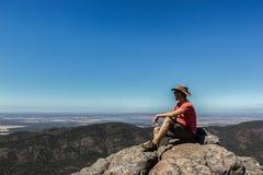 年轻人坐峭壁在Boroka监视,格兰坪国家公园,澳大利亚 免版税库存照片
