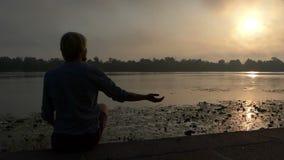 年轻人坐并且思考在河岸在日落在夏天在Slo Mo 股票录像