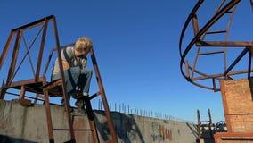 年轻人坐房子的梯子的一个金属平台 股票视频