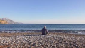 年轻人坐接近蓝色海和投掷的小卵石的海滩 股票视频