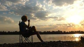 年轻人坐,喝咖啡,在河岸在日落 股票录像