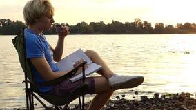 年轻人坐,喝咖啡,微笑,保留一个笔记薄,在河岸 影视素材