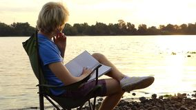 年轻人坐,梦想,微笑,保留一个笔记薄,在河岸 股票录像