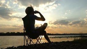 年轻人坐,认为,喝咖啡,在河岸在日落 股票录像