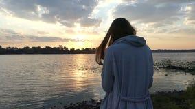 年轻人孕妇在一个精采河岸站立在日落 股票视频