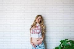 年轻人孕妇在砖墙背景的牛仔裤穿戴了 库存照片