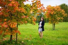 年轻人孕妇在秋天公园 免版税库存图片