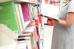 年轻人孕妇阅读书在书店 库存图片
