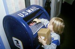 年轻人存款的程序包到美国邮箱里, 图库摄影