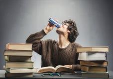 年轻人学习的和饮用的能量饮料 库存图片