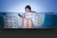 年轻人害怕的和她的20s观看的恐怖片的恐慌亚裔中国妇女在家坐客厅沙发长沙发的电视举行c 库存图片
