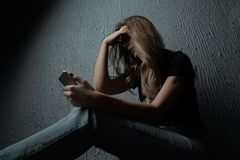 年轻人害怕的和拿着手机的担心的少年女孩,互联网偷偷了靠近受害者被虐待和cyberbullying或者网络 库存图片