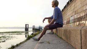 年轻人对Dnipro河岸愉快地坐并且微笑对日落 影视素材