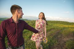 年轻人已婚夫妇 人带领有花花束的一个卷曲女孩  库存图片