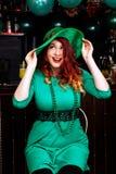 年轻人庆祝帕特里克天乐趣酒吧狂欢节头饰女孩人啤酒鸡尾酒绿色衣裳帽子微笑美丽的妖精 免版税库存图片