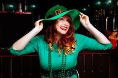 年轻人庆祝帕特里克天乐趣酒吧狂欢节头饰女孩人啤酒鸡尾酒绿色衣裳帽子微笑美丽的妖精 免版税库存照片