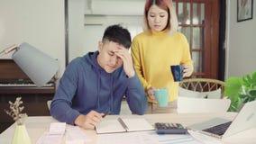 年轻人强调了亚洲夫妇处理的财务,回顾他们的银行帐户使用便携式计算机和计算器在现代家 股票视频