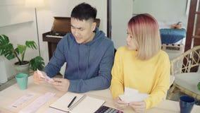 年轻人强调了亚洲夫妇处理的财务,回顾他们的银行帐户使用便携式计算机和计算器在现代家 影视素材