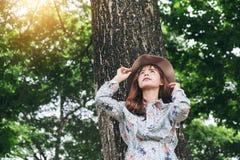 年轻人微笑的亚裔女孩放松在大树下在hol的公园 图库摄影