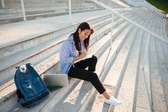 年轻人微笑的亚裔学生画象,采取关于sta的笔记 库存图片