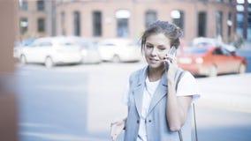 年轻人微笑的俏丽的女孩有一个电话外面户外 免版税图库摄影