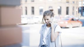 年轻人微笑的俏丽的女孩有一个电话外面户外 库存图片