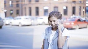 年轻人微笑的俏丽的女孩有一个电话外面户外 免版税库存照片