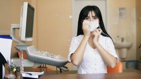 年轻人微笑的女性医生在照相机看并且承担一个防护手术口罩 她坐在桌上 股票视频