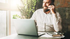 年轻人微笑的有胡子的商人在膝上型计算机,饮用的咖啡前面的桌上,谈话坐手机 库存图片