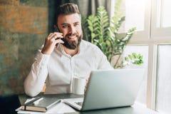 年轻人微笑的有胡子的商人在膝上型计算机,饮用的咖啡前面的桌上,谈话坐手机 免版税库存图片