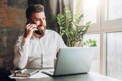 年轻人微笑的有胡子的商人在膝上型计算机,饮用的咖啡前面的桌上,谈话坐手机 免版税库存照片