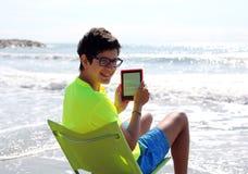 年轻人微笑的白种人男孩在读一本技术e书 库存照片