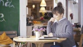 年轻人微笑的逗人喜爱的深色的女孩读在咖啡馆的一本书 免版税库存照片