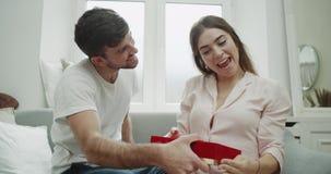年轻人惊奇他的妇女给她的他一个当前箱子,他们在家是,在沙发,她非常被铭记 影视素材