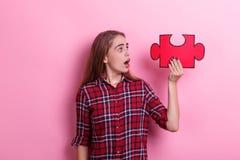 年轻人惊奇的女孩举行在被举的手上的一个大难题并且看它 在桃红色背景 免版税图库摄影