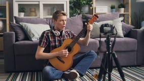 年轻人成功的vlogger记录在家弹吉他和唱在地板上的开会和使用照相机的录影 影视素材