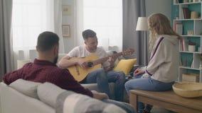年轻人手扶的射击在一个舒适客厅弹他的朋友的吉他 影视素材