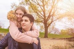 年轻人扛在肩上他的年轻女朋友 免版税库存图片