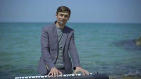 年轻人执行在天蓝色的海岸、海滩或者码头的witm合成器 手,音乐家的手指数字式钢琴的 男 股票视频