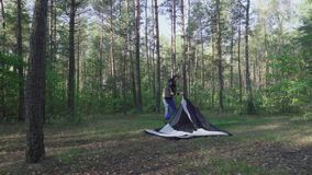 年轻人投入伪装帐篷在黎明在森林在早晨 有长的头发的旅游渔夫做阵营之间 股票视频