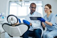 年轻人护理显示在片剂的电子邮件给牙医审查的患者 免版税库存照片
