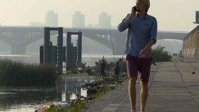 年轻人拔出他的机动性,由它,步行讲话,在河岸 股票视频