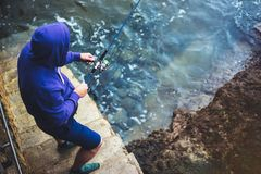 年轻人拿着一根钓鱼竿并且抓在自然的鱼在海背景,渔夫在蓝色oc上度过假期的行家 免版税库存图片