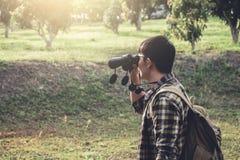 年轻人挑运的旅行使用双筒望远镜 免版税库存图片
