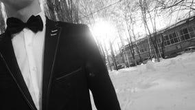 年轻人摆在一套无尾礼服的在冬天反对白色雪,在减速火箭的样式的射击 股票录像