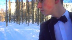 年轻人摆在一套无尾礼服的在冬天反对白色雪,在减速火箭的样式的射击 股票视频