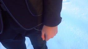 年轻人摆在一套无尾礼服的在冬天反对白色雪,在减速火箭的样式的射击 影视素材